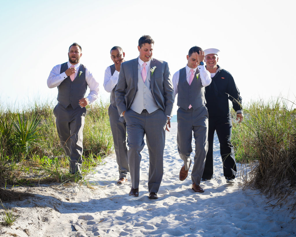 Groom and groomsmen walking the beach after the wedding.